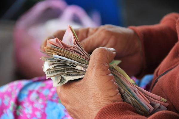 człowiek trzymający banknoty